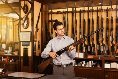 Handsome positive adult male in hunting shop with rifle in hands