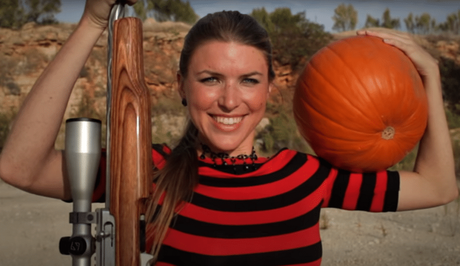 woman teaching people how to carve a pumpkin with a handgun
